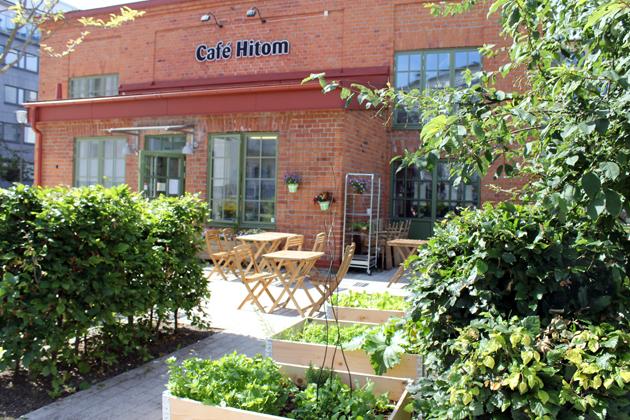 Ett hus i tegel. På huset står det Café Hitom. I förgrunden står det grönskade buskar och några bord och stolar i trä.