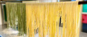Färsk pasta som hänger och torkar på en pinne